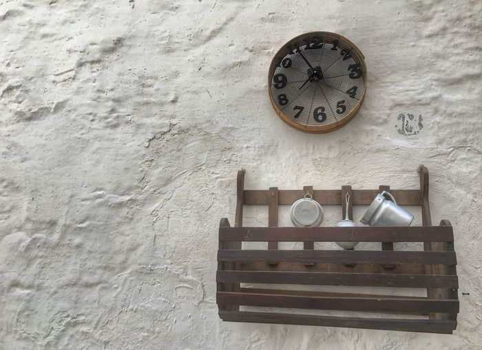 View Of Utensils In Rack And Retro-Styled Clock On White Wall