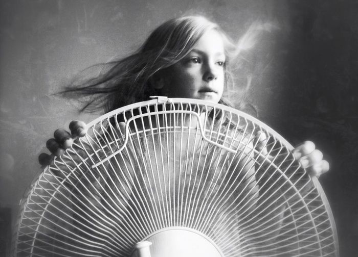 Girl in front of electric fan while looking away