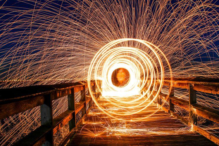 Spinning wire wool on footbridge at night