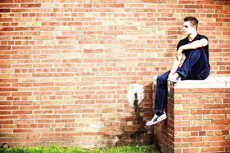 Adult Adults Only Brick Wall Day Full Length Negative Space One Person Outdoors People Sitting Sunlight Young Adult Young Man