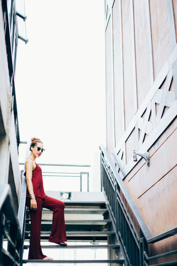 Low angle view of young woman standing on steps against clear sky