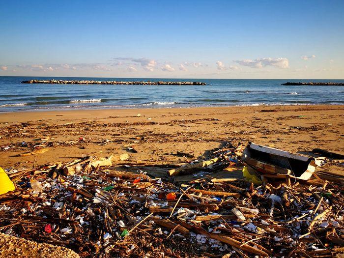 Garbage on beach by sea against sky