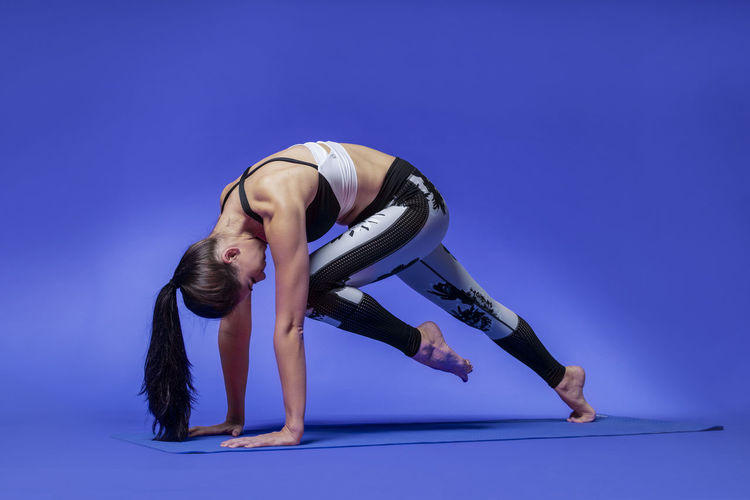Long haired beautiful pilates or yoga athlete does a graceful pose while wearing a tight sports outfit against a bright blue background in a studio Body & Fitness Dance Exercising Silhouettes Stretching Legs Workout Flow Yoga Pose Abdominal Muscles Art Background Exercise Ball Fitness Outfit Long Hair Pilates Pilateslovers Pink Color Pose Pretty Girl Rubber Band Sports Clothing Studio Shot