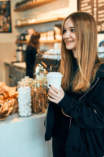 Portrait of a smiling young woman standing in cafe