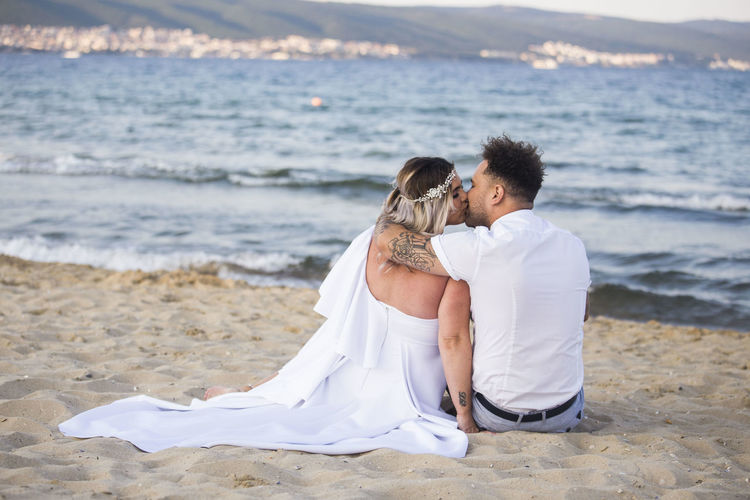 Rear view of newlywed couple kissing while sitting on beach