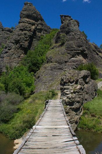 Footpath leading towards mountain against clear sky