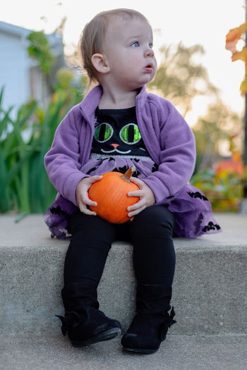 Full length of girl looking away while holding pumpkin on land