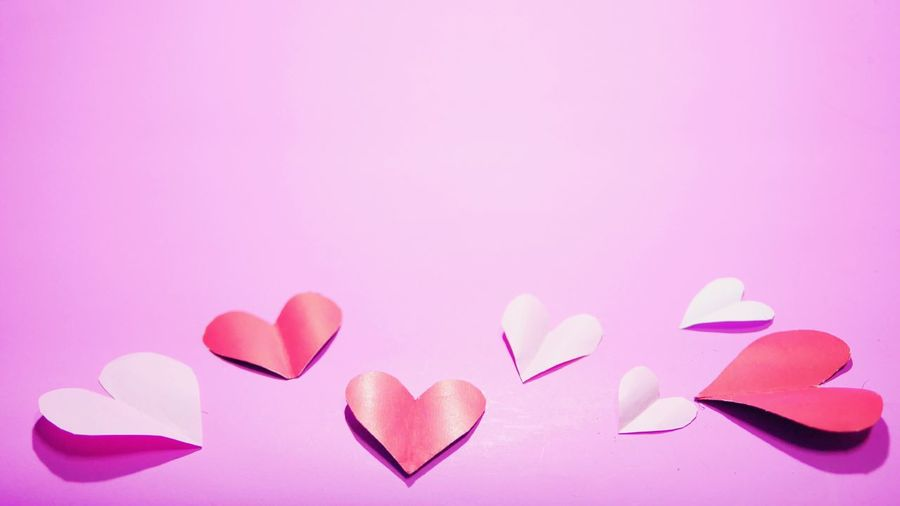 Close-up of heart shape over pink petals on white background