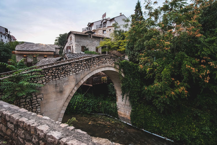 Arch bridge over river amidst trees and buildings against sky