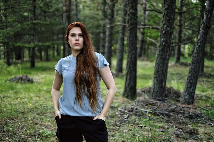 Portrait of young woman standing in forest