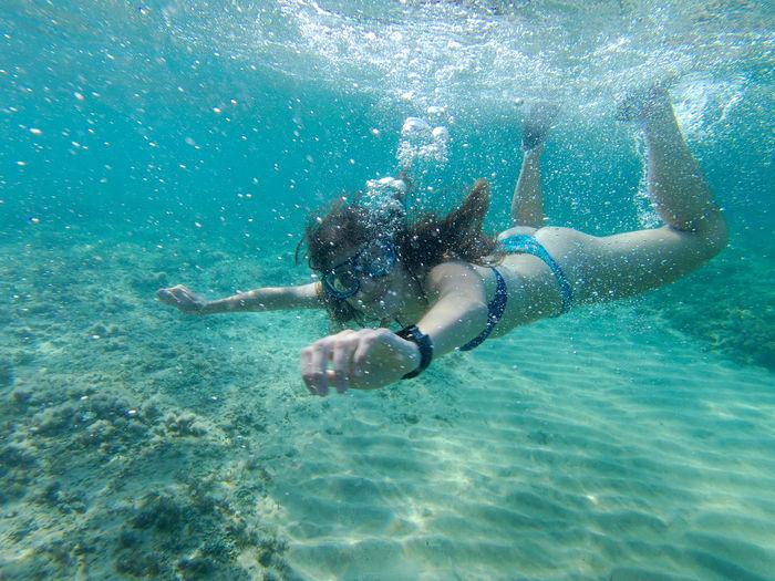 Girl swimming under the sardinian's sea