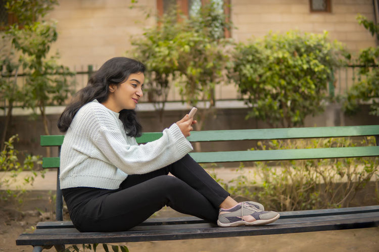 Side view of woman sitting on bench