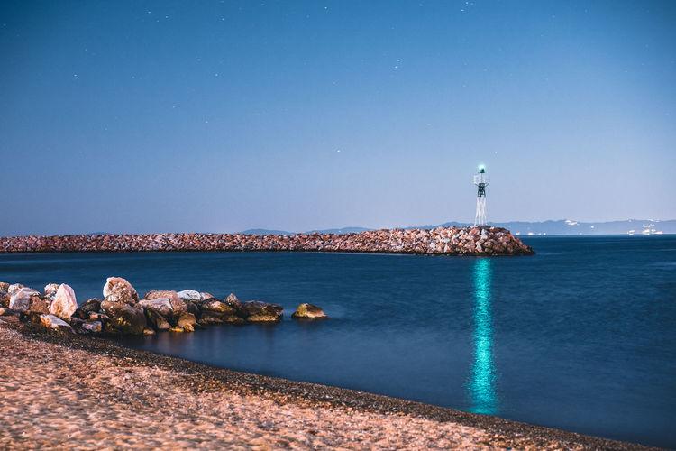 Lighthouse amidst sea and buildings against blue sky