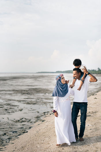 mother and father bonding time with son Asian  Carrying Family Happy Backgrounds Beach Bonding Cheerful Full Length Happiness Hijab Holding Husband Love Malaysia Muddy Muslim Nature Positive Emotion Real People Sand Standing Togetherness Wife