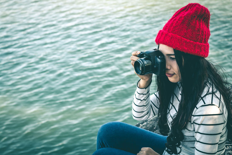 Young woman photographing by lake