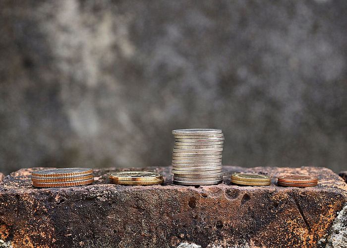 Close-up of coins stacked on brick against wall