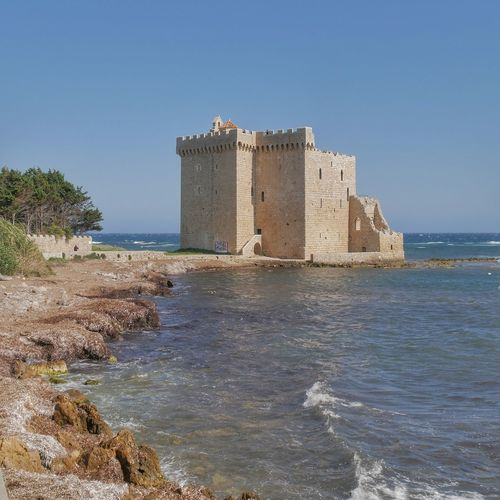 Castle by sea against clear blue sky