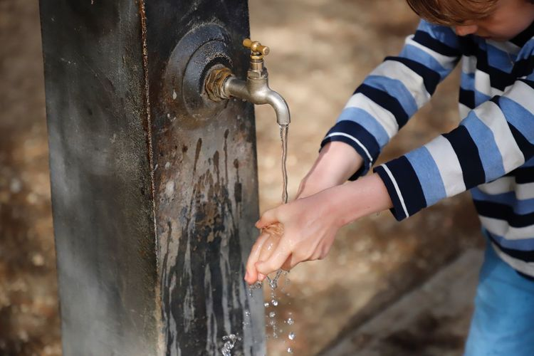 Midsection of boy washing hands at outdoors
