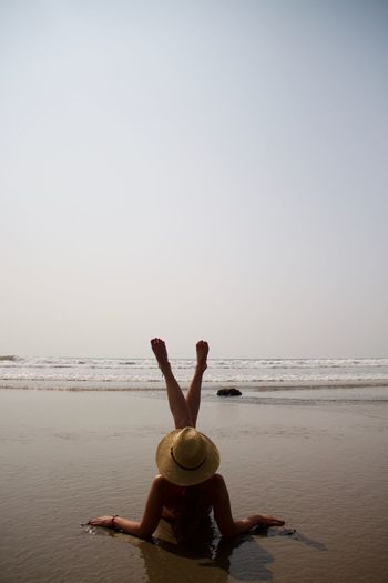 Rear view of woman relaxing on shore against clear sky
