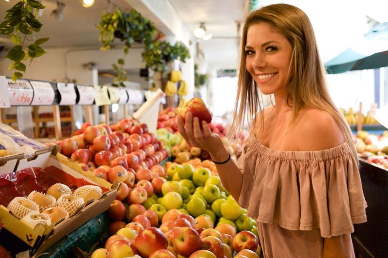Side View Portrait Of Beautiful Woman Smiling While Buying Apples In Supermarket