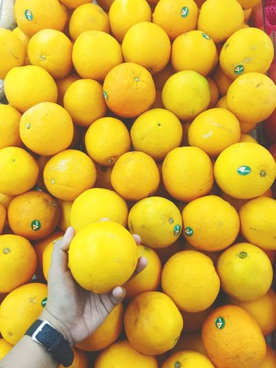 High angle view of hand holding oranges at market