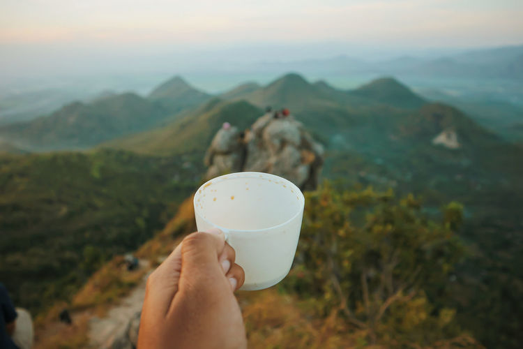 Midsection of person holding ice cream against mountains