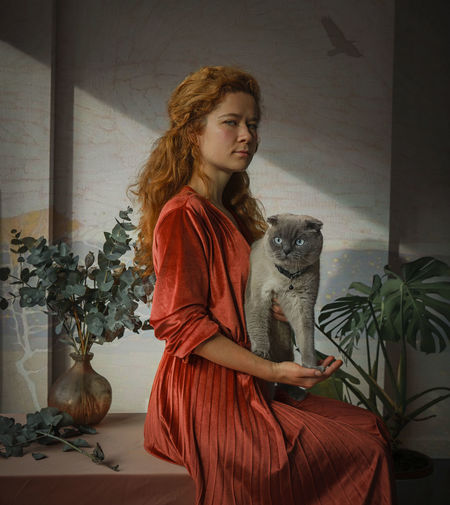 Young woman with cat sitting in a room