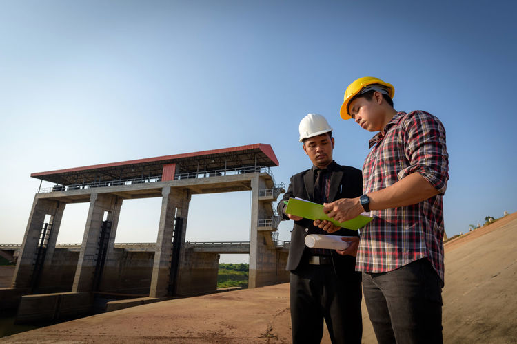 Engineers Standing Against Clear Sky At Construction Site
