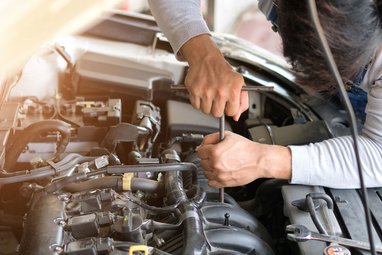 Mechanic repairing engine of car