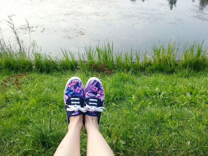 Low Section Of Woman Wearing Sneakers On Grassy Field By Lake