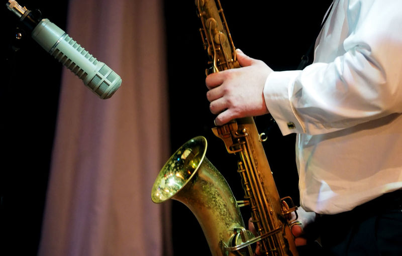 Midsection Of Male Musician Playing Saxophone By Microphone