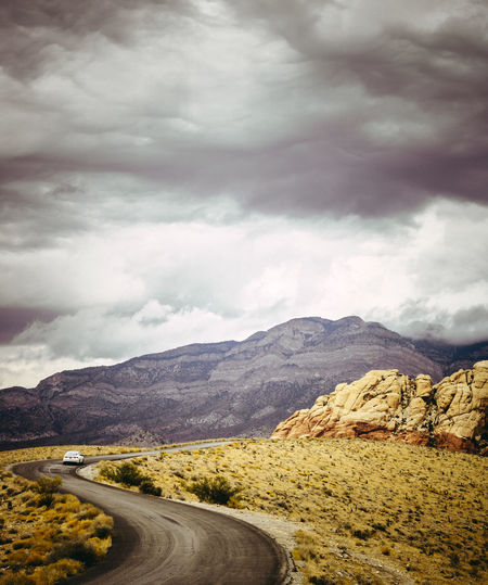 Road leading towards mountains against cloudy sky