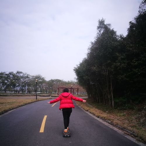 Rear View Full Length Of Woman Skateboarding On Road