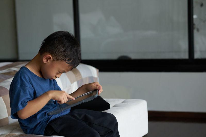 Cute boy using digital tablet at home