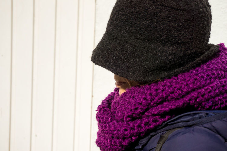 Close-up of woman wearing warm clothing by wall