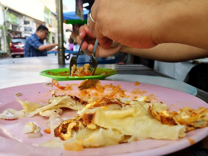 Cropped hands of person having roti canai at concession stand