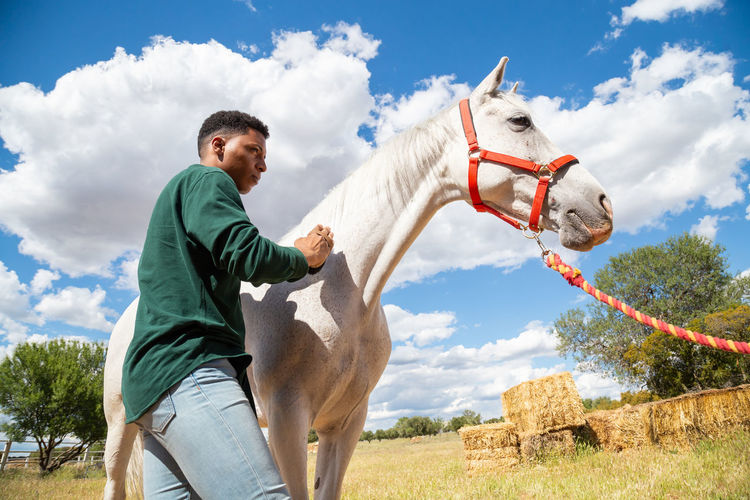 Young man with horse in the background