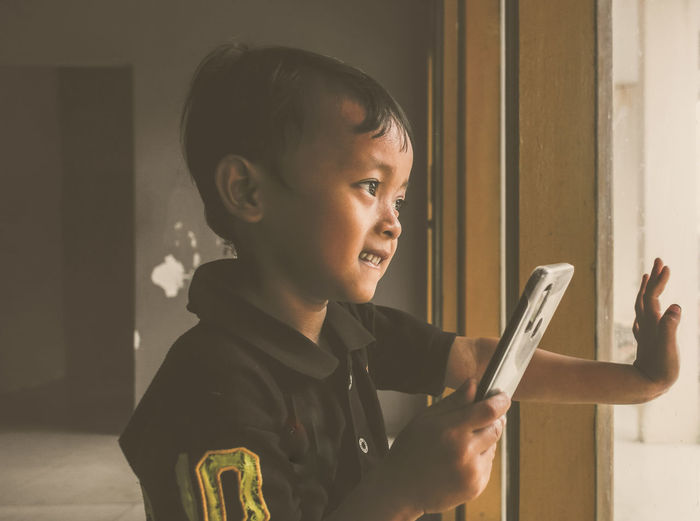 Side view of boy looking through mobile phone at home