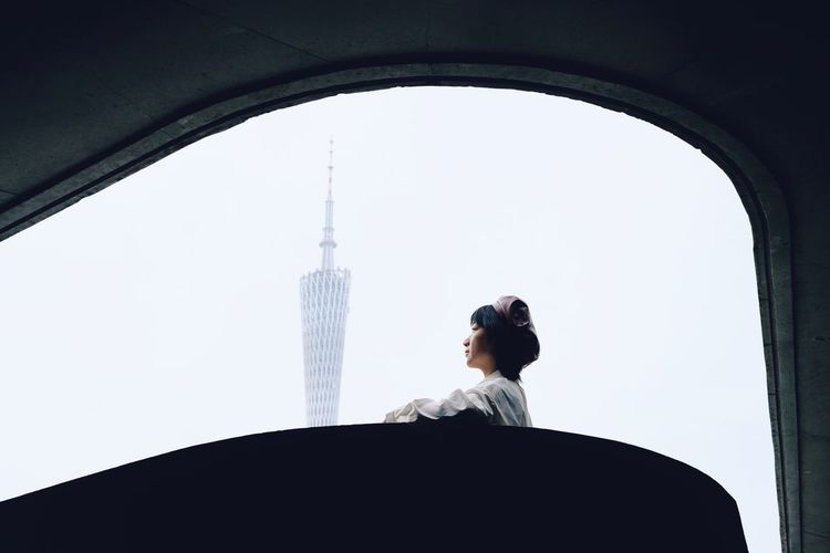Woman standing by buildings against clear sky