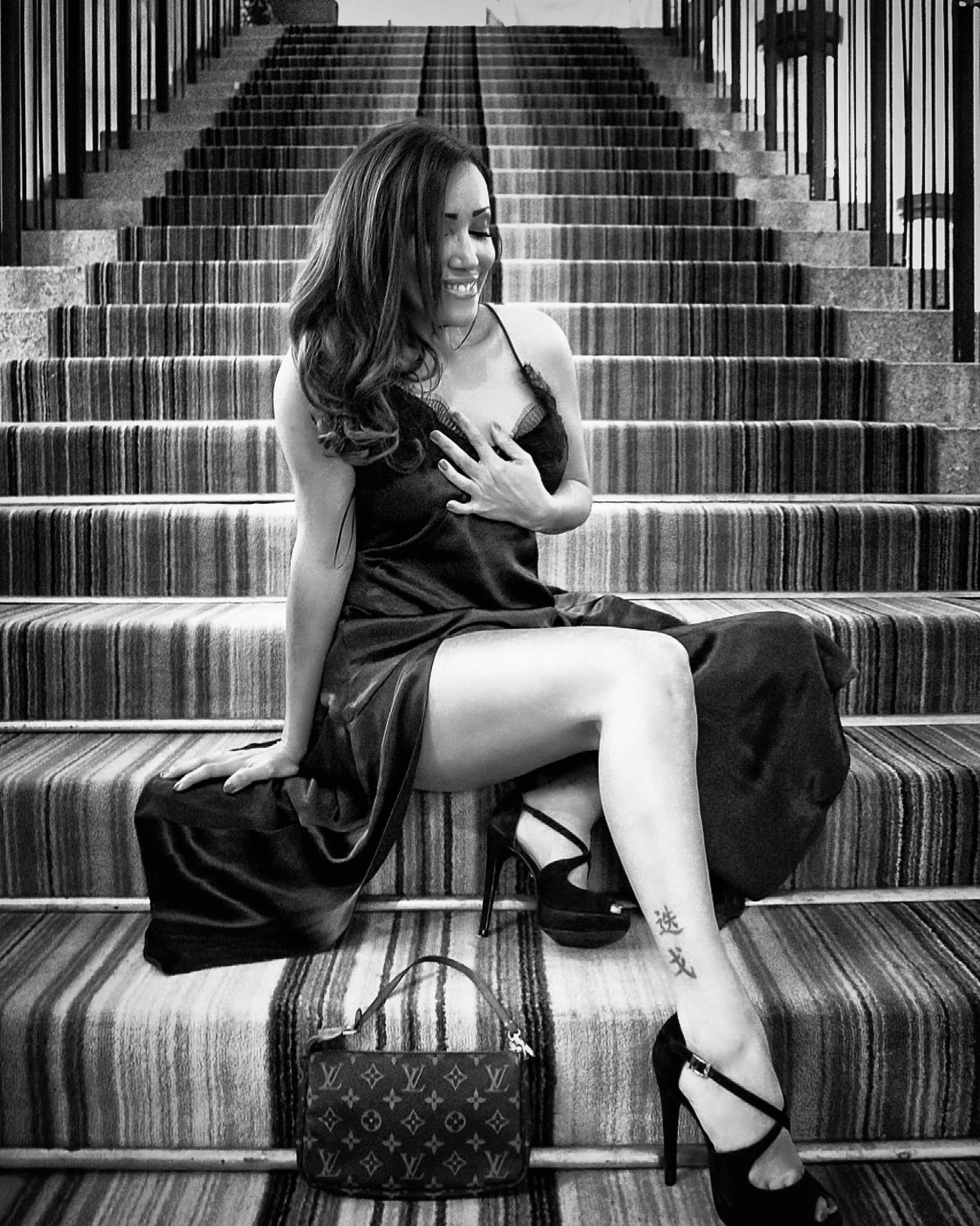 sitting, one person, black and white, women, adult, full length, monochrome photography, black, monochrome, staircase, young adult, lifestyles, fashion, footwear, architecture, photo shoot, female, clothing, person, white, hairstyle, long hair, steps and staircases, seat, portrait, leisure activity, casual clothing, relaxation, emotion, looking, human leg, indoors