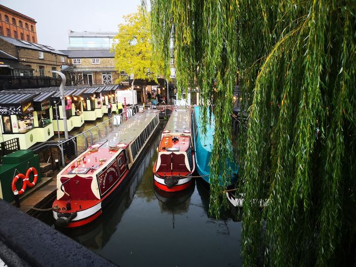 Boats moored on canal in city