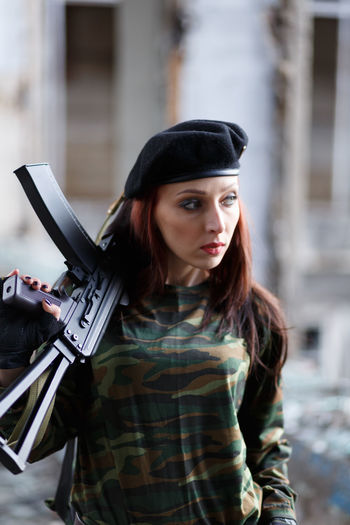 Close-up of mid adult woman holding rifle looking away while standing outdoors