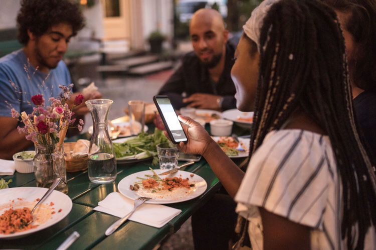 Young woman using smart phone while having dinner with friends during garden party