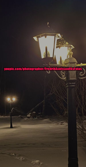 Illuminated street light against sky at night during winter