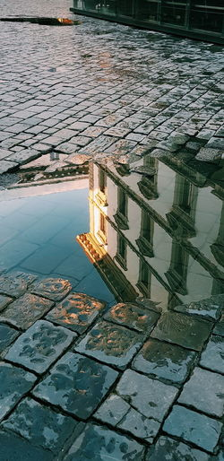 Reflection of building in puddle on lake