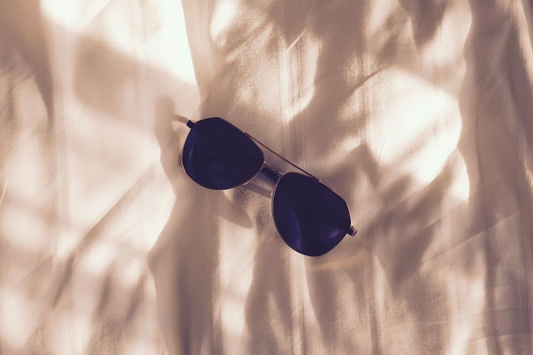 Close-Up Of Sunglasses On Bed