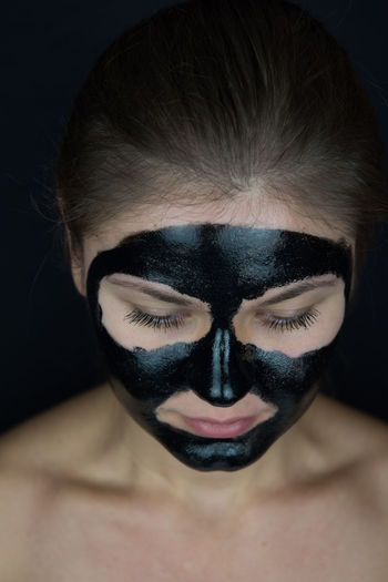 Close-Up Of Young Woman With Facial Mask Against Black Background