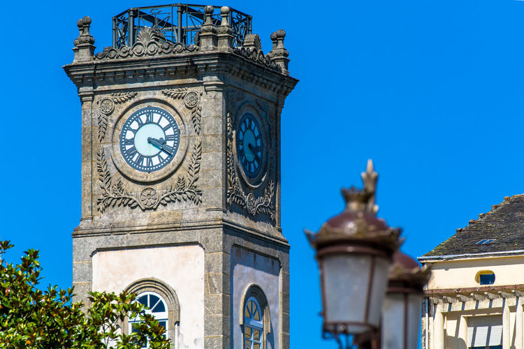 Low Angle View Of Lamp Posts Against Historic Clock Tower