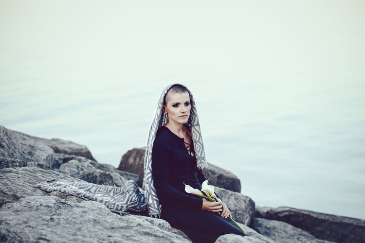 Woman looking away while sitting on rock at beach