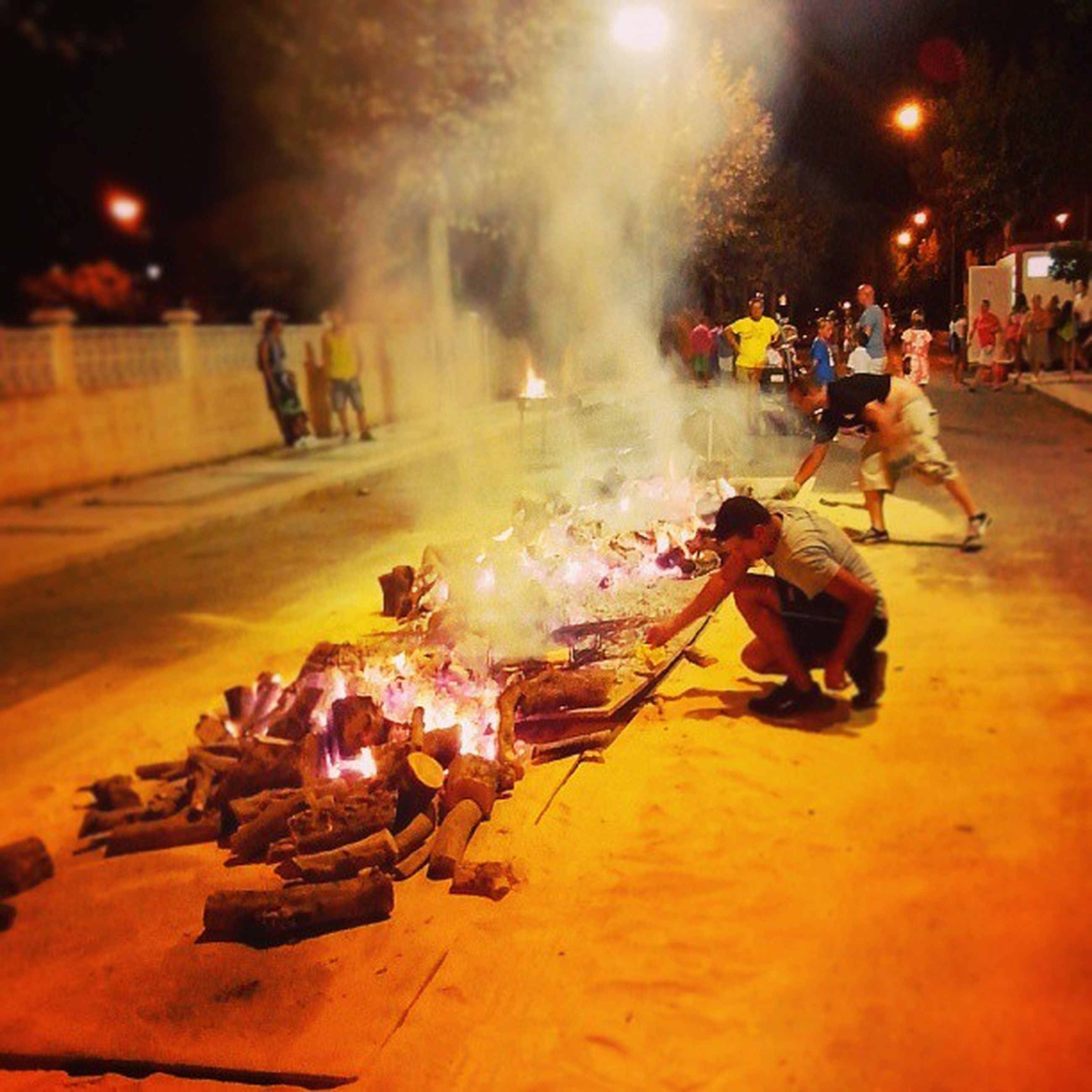 night, illuminated, street, burning, lighting equipment, incidental people, street light, large group of people, flame, outdoors, fire - natural phenomenon, light - natural phenomenon, men, transportation, glowing, motion, building exterior, city, smoke - physical structure